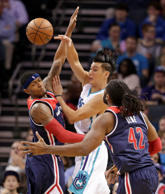 Charlotte Hornets' Jeremy Lin, center, passes the ball as he is trapped by Washi...