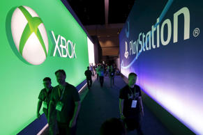 Attendees walk past a Microsoft Xbox sign opposite a Sony PlayStation sign at the Electronic Entertainment Expo, or E3, in Los Angeles, California, United States, June 16, 2015.