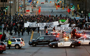 Hundreds of Black Lives Matter demonstrators and supporters occupy the street in front of the federal building, Tuesday, Nov. 24, 2015, in Minneapolis, after marching from the Police Department's Fourth Precinct. The fatal shooting of Jamar Clark, a black man, by a Minneapolis police officer, has pushed racial tensions in the city's small but concentrated minority community to the fore.