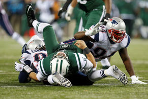 In this Nov. 22, 2012 file photo, Jets quarterback Mark Sanchez is hit by Patriots defensive end Jermaine Cunningham (96) and Justin Francis (94) during the second half of their game. Earlier, Sanchez ran into the back of teammate Brandon Moore and fumbled the ball, which was recovered by the Patriots' Steve Gregory and returned for a touchdown.