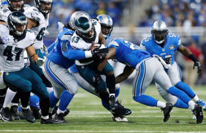Philadelphia Eagles running back Darren Sproles is tackled by Detroit Lions defensive tackle Khyri Thornton, left, and cornerback Nevin Lawson  on Thursday, Nov. 26, 2015, in Detroit.