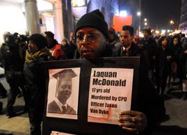 In this Tuesday, Nov. 24, 2015, file photo, a protester holds a sign as people rally for 17-year-old Laquan McDonald, who was shot 16 times by Chicago Police Department Officer Jason Van Dyke in Chicago. McDonald, whose name demonstrators are shouting as they march the streets and plan to shut down the city's glitziest shopping corridor on Friday, lived a troubled life full of disadvantages and at least one previous brush with the law.