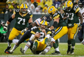 Green Bay Packers' Aaron Rodgers grimaces as he is tackled after recovering a fumble during the second half of an NFL football game against the Chicago Bears Thursday, Nov. 26, 2015, in Green Bay, Wis.