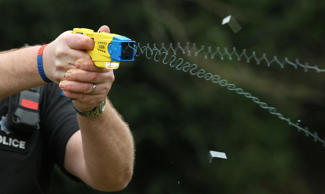 File photo dated 26/02/13 of a police officer using a Taser, as figures suggest that black people are three times more likely to have a Taser used against them than white people.