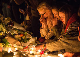 Women mourn at a candlelit and floral memorial to the victims at the Place de Re...