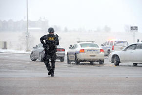 An officer patrols the perimeter during a shooting incident in Colorado Springs, Colo., on Friday, Nov. 27, 2015.