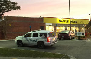 A Biloxi police vehicle sits outside the Waffle House on U.S. 90 in Biloxi, Miss., after an early-morning shooting over a cigarette on Friday, Nov. 27, 2015, left a server dead and a suspect in custody.
