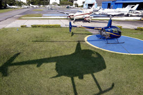A Robson 44 helicopter casts a shadow as it prepares to land at Campo de Marte airport in Sao Paulo April 12, 2015.