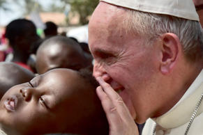 Pope Francis touches children in a refugee camp on November 29, 2015 in Bangui. ...