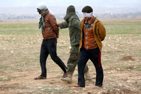 Kurdish Peshmerga forces detain suspected members of ISIL, or Daesh in Arabic, who mixed with a group of villagers fleeing the frontline to a Kurdish-controled area on Nov. 16, 2015 to Sinjar, Iraq.