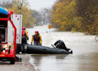 Dallas Fire Department members prepare to put their boat away after rescuing a driver that was stranded after their vehicle was swept by the flood water in Seagoville, Texas, Saturday, Nov. 28, 2015.
