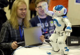 Programmers work on their laptop past 'NAO', a programmable humanoid robot developed by French robotics company Aldebaran Robotics during the 2014 IEEE-RAS International Conference on Humanoid Robots in Madrid on November 19, 2014. The conference theme 'Humans and Robots Face-to-Face' confirms the growing interest in the field of human-humanoid interaction and cooperation, especially during daily life activities in real environments.