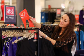 An employee attaches an up to 50 percent discount sign to a clothes rail inside a Debenhams Plc department store on Black Friday in London, U.K., on Friday, Nov. 27, 2015.