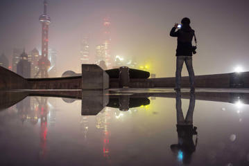A man uses his mobile phone to take pictures of the financial area of Pudong New District (rear) on a smoggy day in Shanghai, China, November 30, 2015. Heavy smog and thick fog engulfed many parts of northern and eastern China on Monday, local media reported.