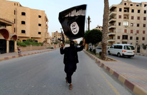 File: A member loyal to the Islamic State in Iraq and the Levant (ISIL) waves an ISIL flag in Raqqa June 29, 2014.