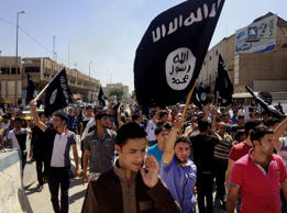 In this June 16, 2014 file photo, demonstrators chant pro-Islamic State group, slogans as they carry the group's flags in front of the provincial government headquarters in Mosul, northwest of Baghdad.