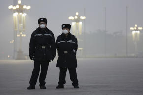 Policemen wear protective masks at the Tiananmen Square on an extremely polluted...