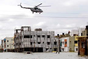 File: An Indian Navy helicopter drops food packets to people surrounded by flood waters following heavy rains in Chennai, Tamil Nadu state, India, Tuesday, Nov.17, 2015.