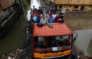 File: Residents stand on a truck after they were rescued from a residential area that was flooded following heavy rains in Chennai, Tamil Nadu state, India, Monday, Nov.16, 2015.