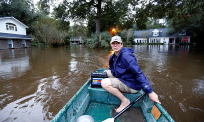 Jeanni Adame rides in her boat as she checks on neighbors seeing if they want to evacuate  in the Ashborough subdivision near Summerville, S.C., after many of their neighbors left, Monday, Oct. 5, 2015.
