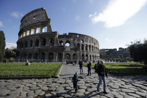Tourists walk outside Rome's Colosseum.