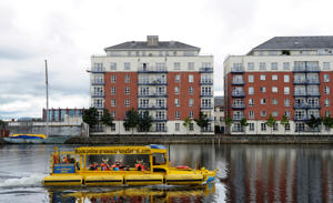 Tourists travel in an amphibious vehicle along the Grand Canal basin in Dublin, Ireland.