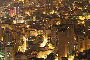 Apartment and office buildings stand crowded together and illuminated at night in Monaco.
