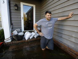Sean Nance walks through floodwaters carrying some work clothes as he evacuates ...