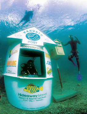 TO GO WITH VANUATU-POSTA scuba diver mans the world's first underwater post office as a snorkeller uses the aquatic post box off the coast of Hideaway Island in Vanuatu, 30 June 2003, which was established to celebrate the 83-island archipelago's staus as a marine paradise. Customers buy special waterproof postcards available on land before diving three metres down to have their mail embossed with a waterproof stamp whilst being surrounded by coral and multicoloured fish. AFP PHOTO/Craig BERULDSEN (Photo credit should read CRAIG BERULDSEN/AFP/Getty Images)