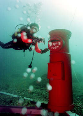TOK01:SUSAMI,JAPAN,2MAY99 - A diver drops a postcard into an undersea mailbox off the coast of Susami, in the western Japanese prefecture of Wakayama April 28. The mailbox was installed at a depth of 10 metres April 23 as a part of a marine sports festival event and can be used to send mail. Divers can post a 150 yen (US$1.2) waterproof plastic postcard into the box and a local diving shop staff member picks up cards once a day as part of regular mail service.