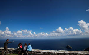 Tourists admire the Aegean see from the top of the village of Hora, in the Greek island of Amorgos.