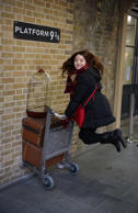 A tourist re-enacts a scene from Harry Potter at Kings Cross station in London.