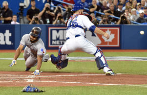 Texas Rangers center fielder Delino DeShields (left) scores a run past Toronto Blue Jays catcher Russell Martin (55) in the third inning in game one of the ALDS at Rogers Centre.