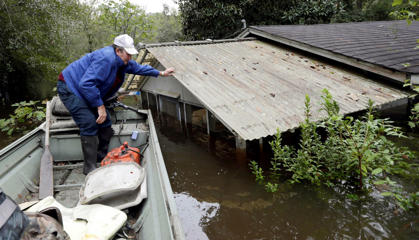 Florence, S.C. resident Jackie Lee surveys the flooding to his property on Roundtree Road along the Lynches River near Effingham, S.C., Tuesday, Oct. 6, 2015, where houses and cars are swamped following record rainfall in the state.  The Carolinas saw sunshine Tuesday after days of inundation, but it could take weeks to recover from being pummeled by a historic rainstorm that caused widespread flooding and multiple deaths.(AP Photo/Gerry Broome)