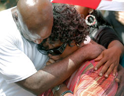 Judy Scott is comforted Thursday, July 9, 2015, by Alfred Smalls at the site in ...