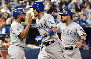 Texas Rangers catcher Robinson Chirinos (middle) celebrates with teammates Delino DeShields (left) and Rougned Odor (right) after hitting a two-run home run against the Toronto Blue Jays in the fifth inning in game one of the ALDS at Rogers Centre.