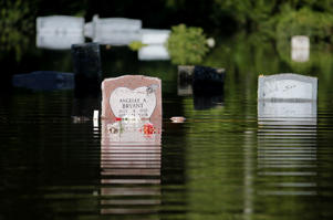Tombstones reflect in the floodwaters at Canaan United Methodist Church near Summerville, S.C., Thursday, Oct. 8, 2015. The church had a couple caskets come out of the ground at their cemetery beside the church during the flooding this week. (AP Photo/Mic Smith)