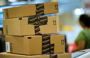 Amazon.com employees package merchandise for shipment inside the Amazon.com dist...