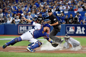 Texas Rangers' Delino DeShields (right) slides safely into home plate past the tag of Toronto Blue Jays' catcher Russell Martin during third inning.