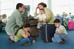 Multi-ethnic family waiting in airport.