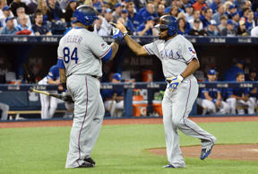 Texas Rangers center fielder Delino DeShields (right) celebrates with designated hitter Prince Fielder (84) after scoring a run against the Toronto Blue Jays in the first inning in game two of the ALDS at Rogers Centre.