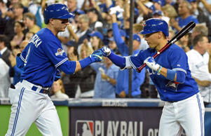 Toronto Blue Jays shortstop Troy Tulowitzki (2) is congratulated by teammates after scoring a run against the Texas Rangers in the second inning in game two of the ALDS at Rogers Centre.