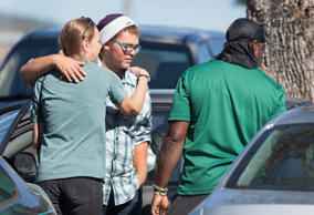 Umpqua Community College shooting survivor Mathew Downing (C) is greeted as he a...