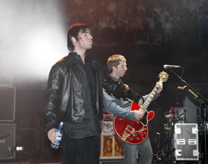 Liam and Noel Gallagher of the pop group 'Oasis' perform on stage for the 'Teenage Cancer Trust' at the Royal Albert Hall on February 7, 2002 in London.