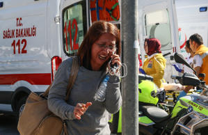 A survivor cries as she talks on a cellphone after an explosion during a peace m...