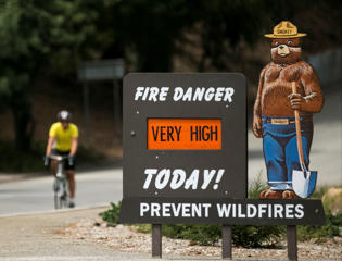 "A Smokey Bear ""Very High"" fire danger sign is posted at the entrance to Griffith Park in Los Angeles Thursday, Sept. 10, 2015."