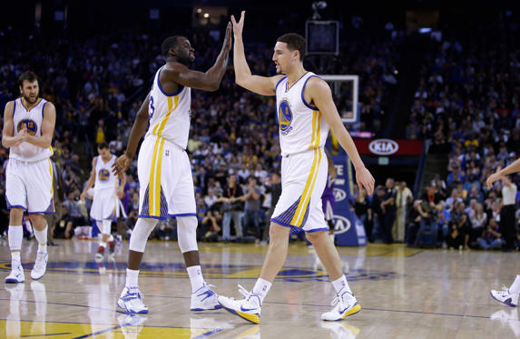OAKLAND, CA - JANUARY 23: Klay Thompson #11 of the Golden State Warriors is congratulated by Draymond Green #23 after he made a basket in the third quarter of their game against the Sacramento Kings at ORACLE Arena on January 23, 2015 in Oakland, California. Thompson scored 37 points in the third quarter to set a NBA record. NOTE TO USER: User expressly acknowledges and agrees that, by downloading and or using this photograph, User is consenting to the terms and conditions of the Getty Images License Agreement.