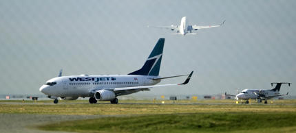 FILE: A West Jet Boeing 737-700 aircraft (L) departs Vancouver International Air...