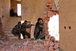 Kurdish People's Protection Units (YPG) fighters take up positions inside a damaged building in al-Vilat al-Homor neighborhood in Hasaka city, as they monitor the movements of Islamic State fighters who are stationed in Ghwayran neighborhood in Hasaka city, Syria July 22, 2015.
