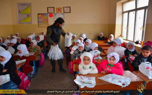 In this photo released on Jan. 11, 2015, by a militant website, which has been verified and is consistent with other AP reporting, an Islamic State militant, center, distributes plastic bags full of stationery and other gifts to Iraqi young students at a school classroom in Mosul, northern Iraq.
